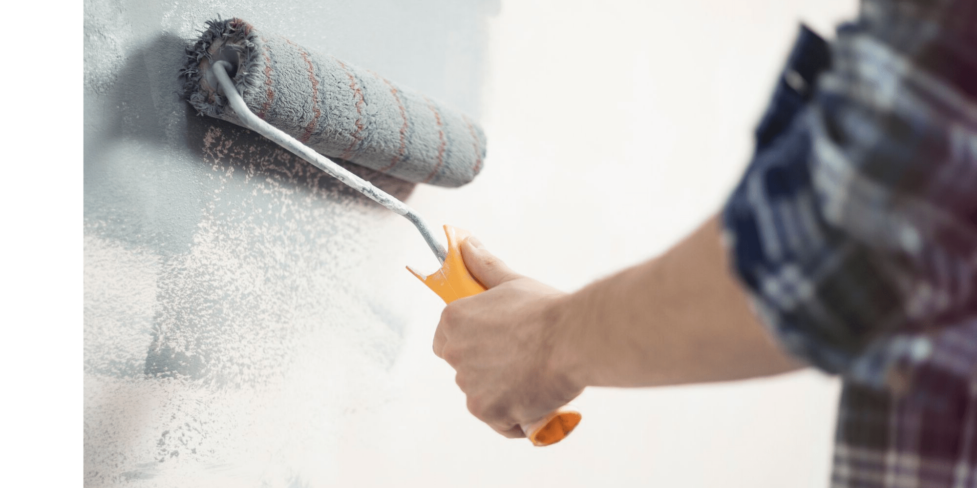 A man rolling grey paint on a wall with a paint roller.