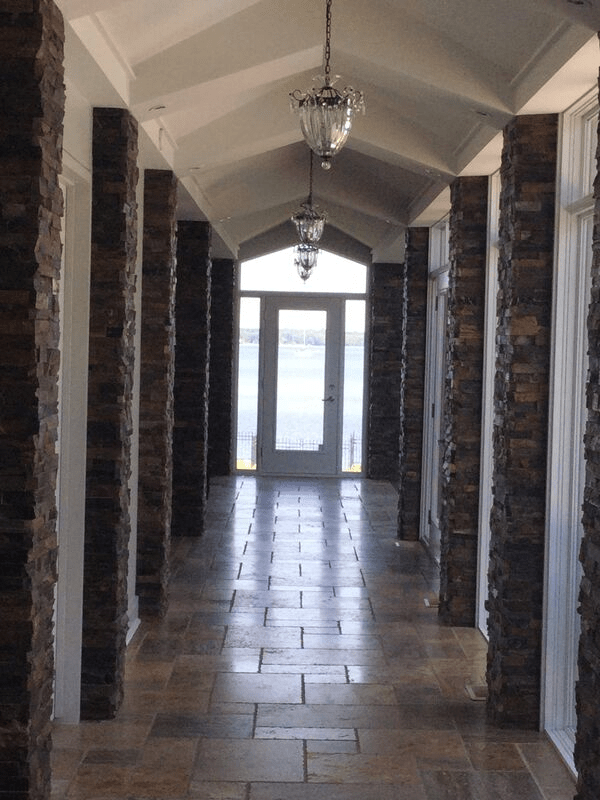 A long hallway with stonework pillars with a painted white ceiling.