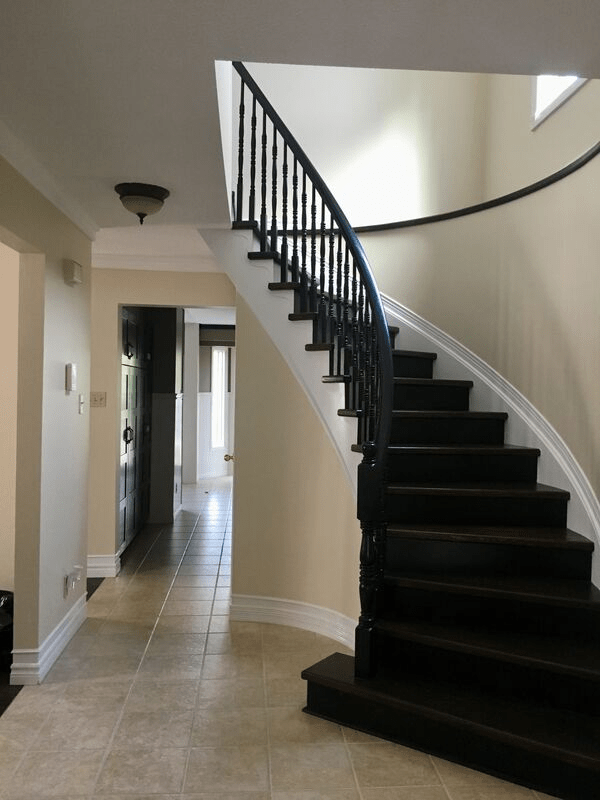 A spiral staircase in a hallway with freshly painted beige walls with white trim.