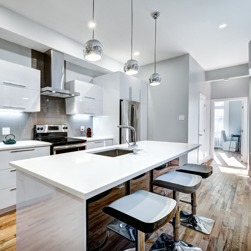 Bright open kitchen with light grey walls and white cabinets.