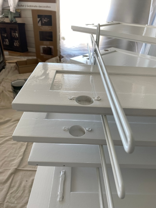 Freshly painted white kitchen cabinet doors on a drying rack.