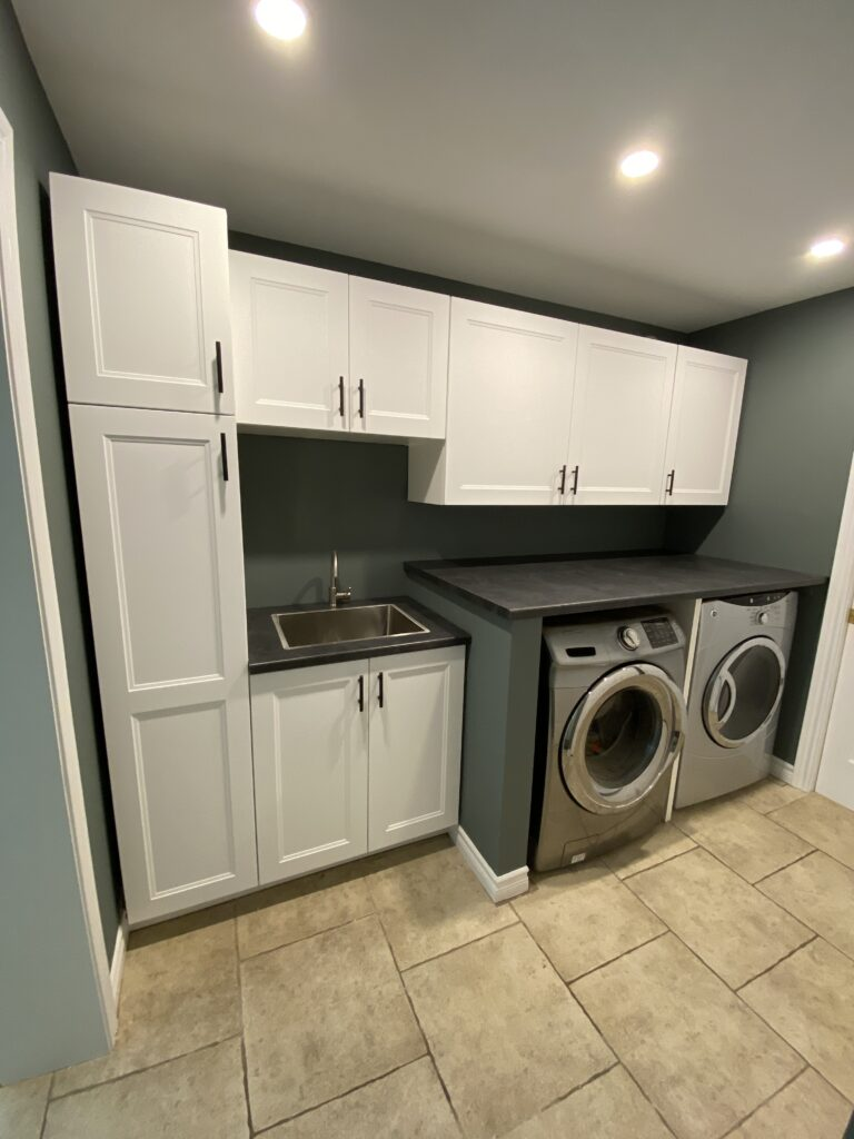 Painted cabinets in a laundry room with freshly painted walls in a deep sage green.