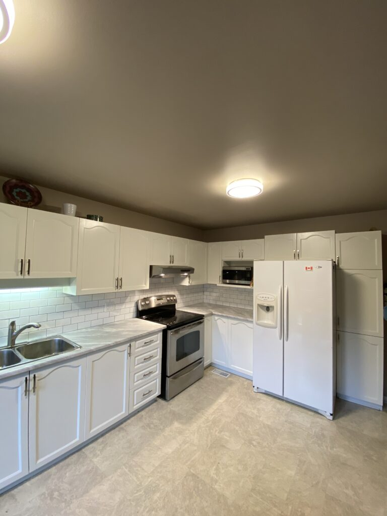 Freshly painted white cabinets in a modern kitchen with a tile backsplash.