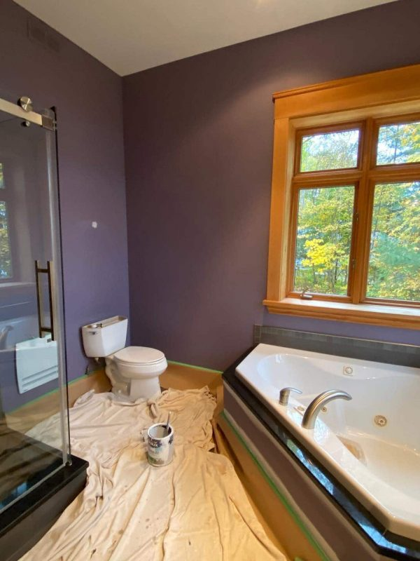 Freshly painted purple bathroom with wooden molding.