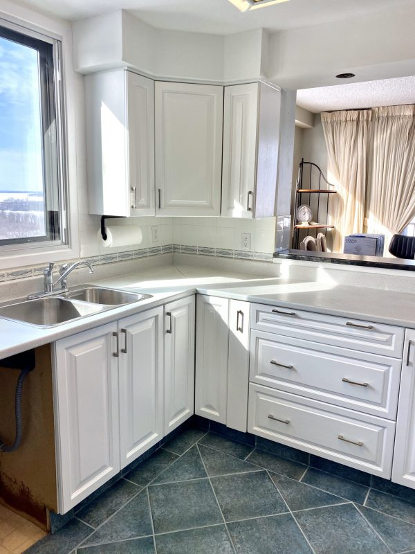 Freshly painted white kitchen cabinets in a modern kitchen.